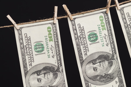 cleaning debt: Hundred Dollar Bills Hanging From a Clothesline on a Dark Background.