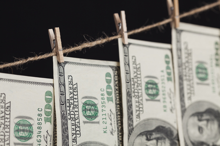 Hundred Dollar Bills Hanging From a Clothesline on a Dark Background. photo