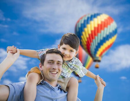 piggy back: Father and Son Playing Piggyback with Hot Air Balloons Floating Behind Them  Stock Photo