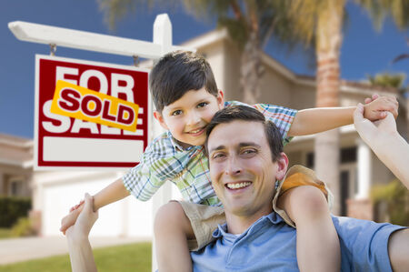 Mixed Race Father and Son Celebrating with a Piggyback in Front Their House and Sold Real Estate Sign  photo