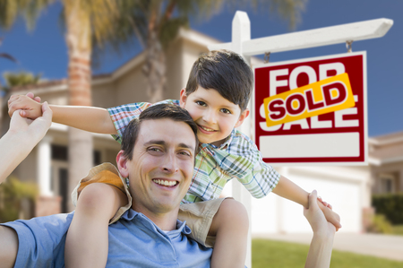 head home: Mixed Race Father and Son Celebrating with a Piggyback in Front Their House and Sold Real Estate Sign