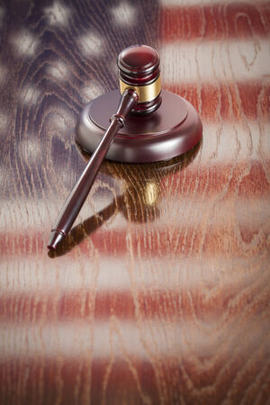 room for text: Wooden Gavel Resting on American Flag Reflecting Table. Stock Photo