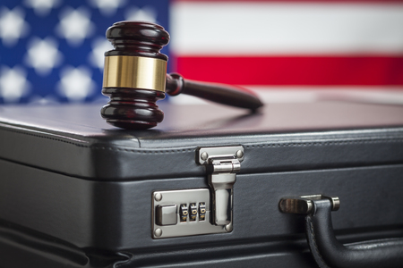Leather Briefcase and Gavel Resting on Table with American Flag Behind. photo