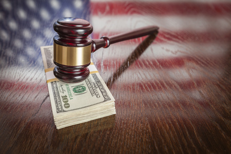 Wooden Gavel Resting on Stack of Money with American Flag Reflection on Table. photo