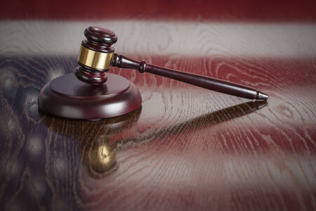 ruling: Wooden Gavel Resting on American Flag Reflecting Table. Stock Photo