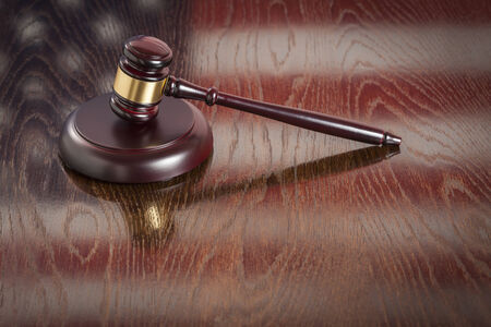 Wooden Gavel Resting on American Flag Reflecting Table. photo