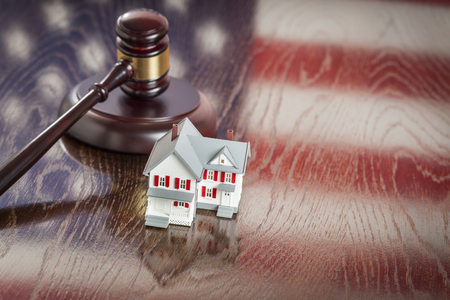 bank owned: Small House and Gavel on Wooden Table with American Flag Reflection. Stock Photo