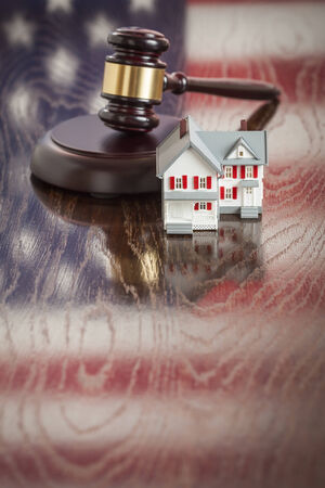 Small House and Gavel on Wooden Table with American Flag Reflection. photo