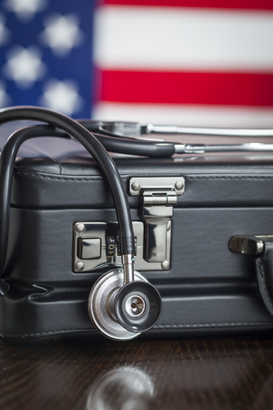attache: Leather Briefcase and Stethoscope Resting on Table with American Flag Behind.