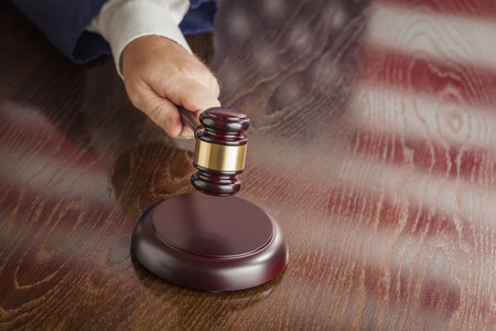 Judge Slams His Gavel and American Flag Table Reflection. photo