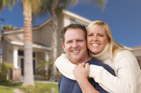 Happy Couple Hugging in Front of Beautiful House. Stock Photo - 29627267