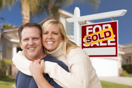 Happy Couple Hugging in Front of Sold Real Estate Sign and House. Stock Photo - 29627271