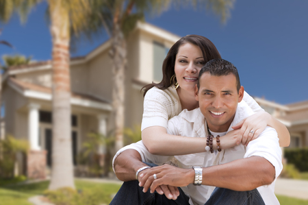 new age: Young Happy Hispanic Young Couple in Front of Their New Home. Stock Photo