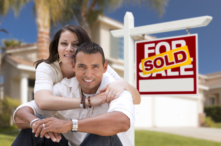 real estate sign: Young Happy Hispanic Young Couple in Front of Their New Home and Sold For Sale Real Estate Sign.