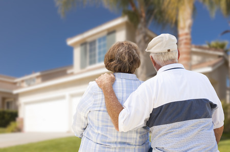 house shopping: Happy Senior Couple From Behind Looking at Front of House. Stock Photo
