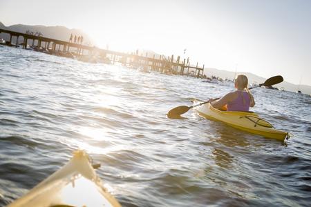 kayaker: Woman Kayaking on Beautiful Peaceful Mountain Lake at Sunset.