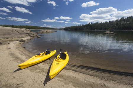 Pair of Yellow Kayaks on a Beautiful Mountain Lake Shore. photo
