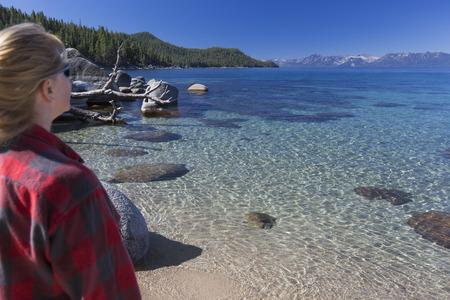 shoreline: Mujer que mira sobre Hermosa Agua Clara la costa del Lago Tahoe.