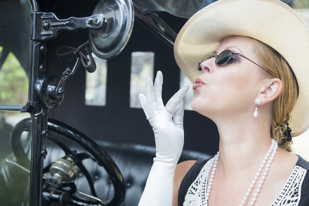 Attractive Young Woman in Twenties Outfit Checking Makeup in Antique Automobile. Stock fotó
