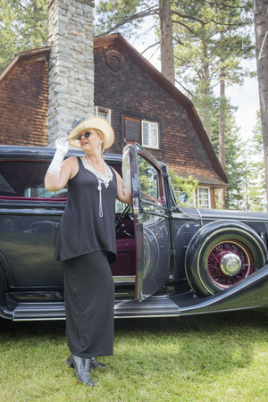 twenties: Attractive Young Woman in Twenties Outfit Near Antique Automobile.