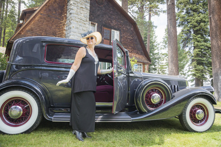 Attractive Young Woman in Twenties Outfit Near Antique Automobile.