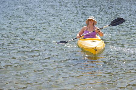 kayaker: Woman Kayaking on Beautiful Peaceful Mountain Lake.