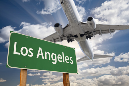 sunshine state: Los Angeles Green Road Sign and Airplane Above with Dramatic Blue Sky and Clouds. Stock Photo