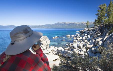 shoreline: Mujer que mira sobre Hermosa Clear Water costa del Lago Tahoe. Foto de archivo