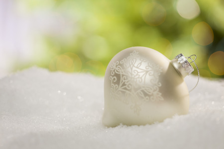 Beautiful White Christmas Ornament on Snow Over an Abstract Background. photo