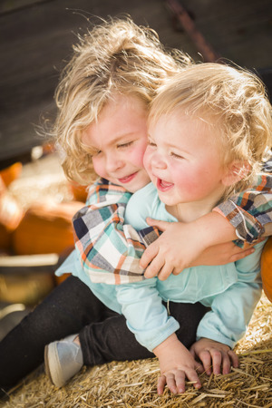 Sweet Little Boy Plays with His Baby Sister in a Rustic Ranch Setting at the Pumpkin Patch. photo