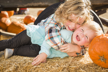 playing the market: Sweet Little Boy Plays with His Baby Sister in a Rustic Ranch Setting at the Pumpkin Patch. Stock Photo