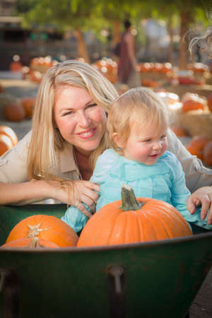Adorable Young Mother and Daughter Enjoys a Day at the Pumpkin Patch. photo