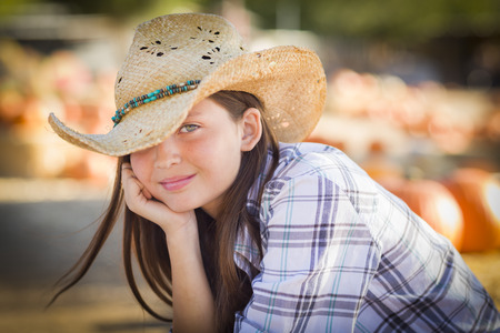 cowgirl and cowboy: Pretty Preteen Girl Wearing Cowboy Hat Portrait at the Pumpkin Patch in a Rustic Setting.