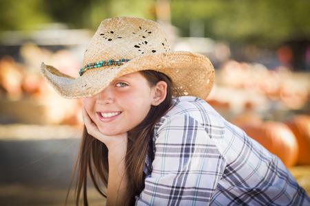 wheel barrel: Pretty Preteen Girl Wearing Cowboy Hat Portrait at the Pumpkin Patch in a Rustic Setting.