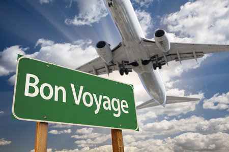 Bon Voyage Green Road Sign and Airplane Above with Dramatic Blue Sky and Clouds. Banco de Imagens