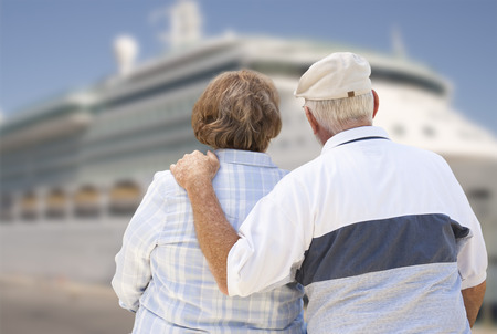 disembarking: Senior Couple On Shore Facing and Looking at Docked Cruise Ship.