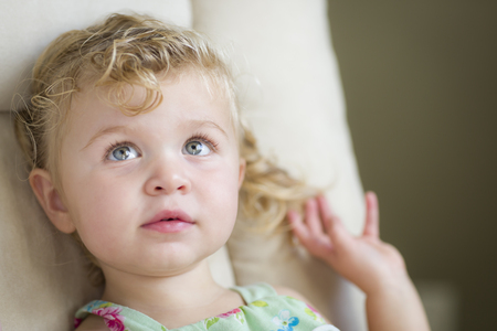 blonde haired: Adorable Blonde Haired and Blue Eyed Little Girl Sitting in Chair. Stock Photo