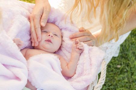 Gentle Hands of Mother Caressing Her Newborn Baby Girl in Pink Blanket. Banco de Imagens - 32257665