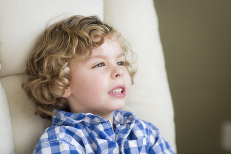 baby 4 5 years: Cute Young Blonde Boy Daydreaming and Sitting in Chair.