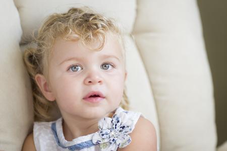 blonde yeux bleus: Adorable Blonde aux cheveux et aux yeux bleus Petite fille assise dans un fauteuil.