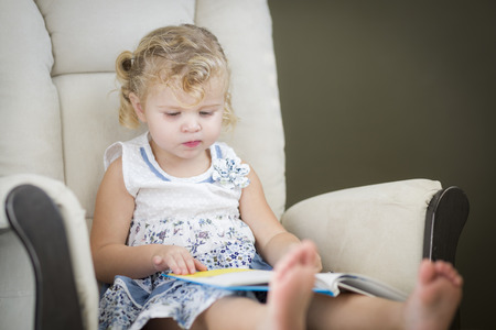 blonde haired: Adorable Blonde Haired Blue Eyed Little Girl Reading Her Book in the Chair.