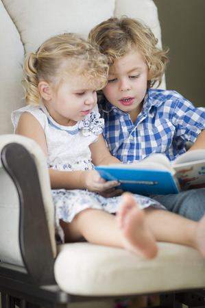 2 year old: Cute Young Brother and Sister Reading a Book Together in a Chair. Stock Photo