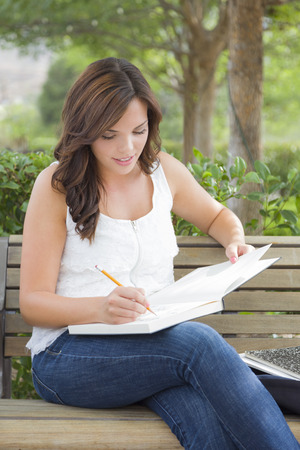 sitting on a bench: Attractive Young Adult Female Student on Bench Outdoors with Books and Pencil.