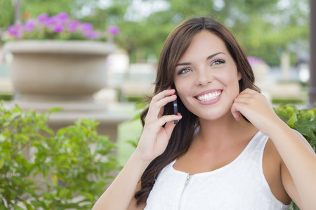 Attractive Young Adult Female Talking on Cell Phone Outdoors on Bench. photo