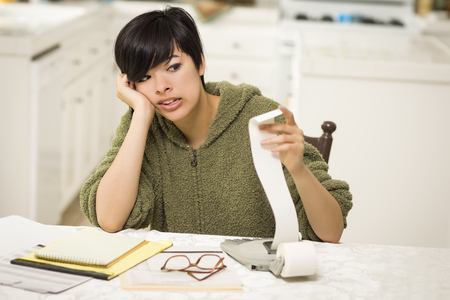 agonizing: Multi-ethnic Young Woman Agonizing Over Financial Calculations in Her Kitchen.
