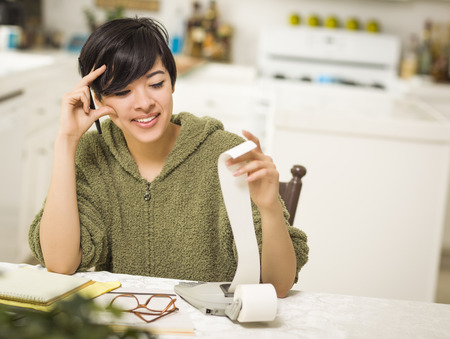 relieved: Multi-ethnic Young Woman Relieved and Smiling Over Financial Calculations in Her Kitchen.