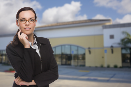 vacant: Attractive Serious Mixed Race Woman In Front of Vacant Commercial Retail Building.