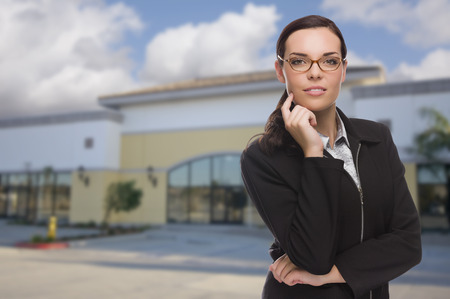 wholesale: Attractive Serious Mixed Race Woman In Front of Vacant Commercial Retail Building.