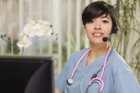 Attractive Mixed Race Young Woman Nurse Practitioner or Doctor at Her Computer Monitor. Фото со стока
