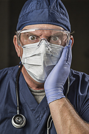 Stunned Male Doctor or Nurse with Protective Wear and Stethoscope. photo